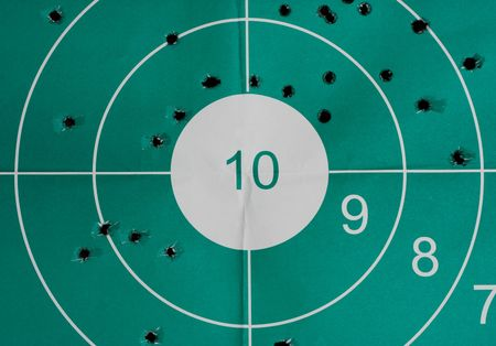 Many bullet holes in the target and intact bullseye - inaccuracy concept