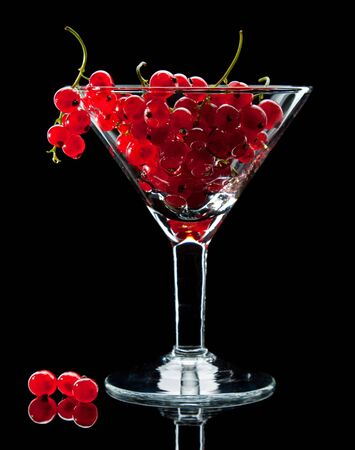 Close-up of red currant in wineglass isolated over black photo