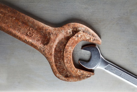 Wrenches over metal plate - age and size contrast, opposition concept