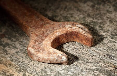 Macro of corroded old spanner over battered wood, grungy style Stock Photo - 10686961