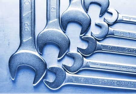 Macro of wrenches metallic blue tinted on stainless steel background photo