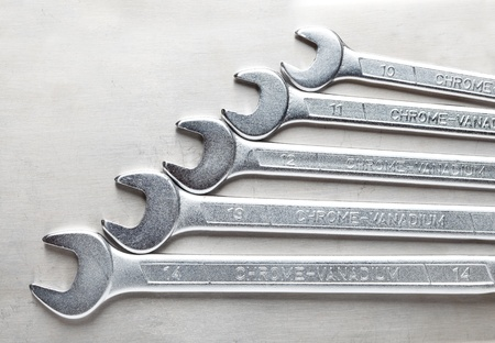 Macro of wrenches tool kit over steel background photo