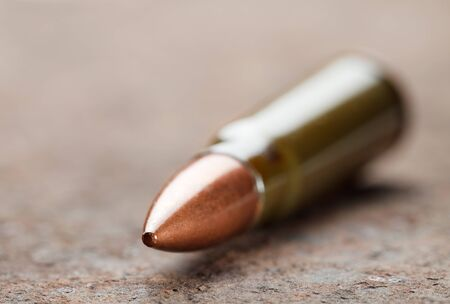 Macro of kalashnikov bullet over corroded iron plate photo