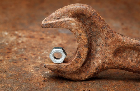 unsuitable: Macro of small stainless nut and old grunge wrench - concept of difference