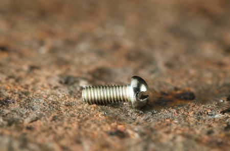 corroded: Small stainless nut over corroded iron plate