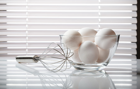 wire whisk: Wire whisk and glass bowl full of raw eggs over white venetian blind background Stock Photo