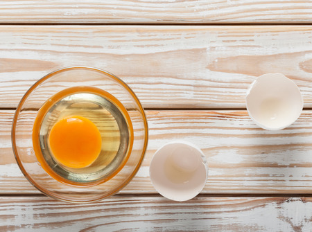 egg white: Top view of yolk and egg white in glass bowl on white weathered wooden table Stock Photo