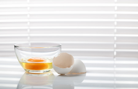 jalousie: Broken egg in glass bowl ready for whisking on kitchen table near window with jalousie