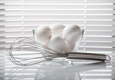 jalousie: Still life of metal whisk and eggs on kitchen table in front of window jalousie