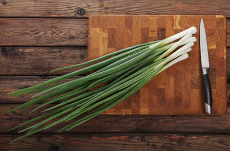 potherbs: Top view of spring onions bunch ready to cutting on chopping board