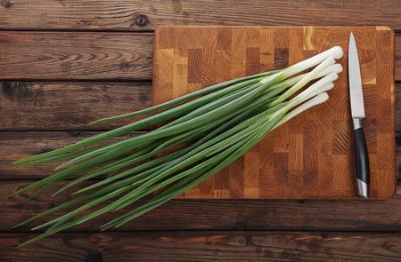 cebolla: Vista superior de cebollas de primavera ramo listo para el corte en tajadera Foto de archivo