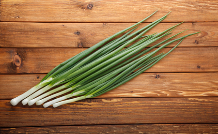 potherbs: Top view on row of green onions on rustic wooden background Stock Photo