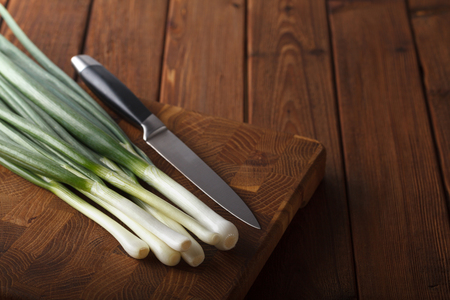 Closeup of green onions bunch and knife on chopping block over rustic wooden table