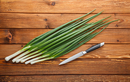 potherbs: From above on spring onions in line and knife on rough wooden table