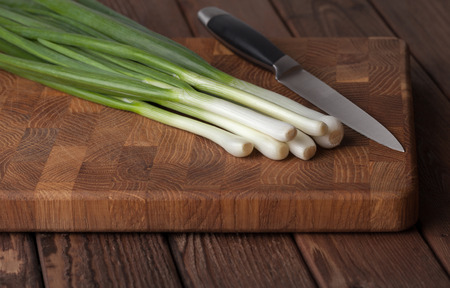 breadboard: Low angle view of spring onions bunch and knife on breadboard over wooden kitchen table Stock Photo