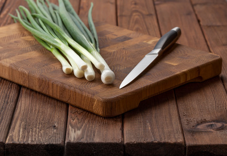 breadboard: Knife and onion bunch ready to cutting on breadboard on rustic wooden table Stock Photo