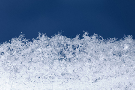 hoarfrost: Macro of light snowflakes in snowbanks structure over blue background at christmas night Stock Photo