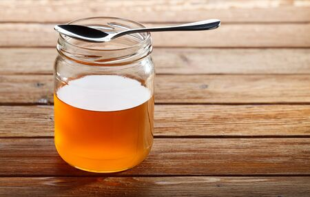 treacle: Glass jar with pure fresh honey and small spoon on top Stock Photo