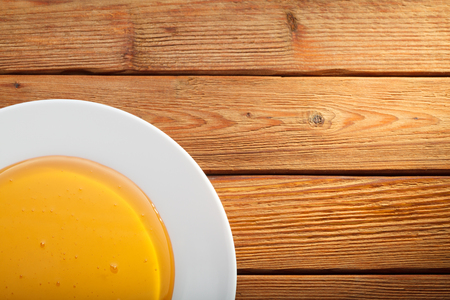 treacle: Closeup top view of fresh golden honey in white plate on wooden table Stock Photo