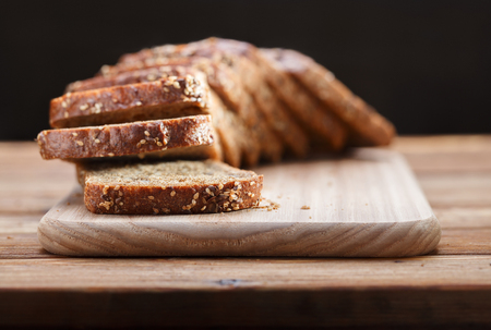 Low point of view on sliced rustic homemade bread with grains on breadboard over wood table Stock Photo