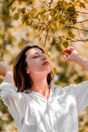 Random photo. A beautiful girl in a white shirt straightened her hair with her hands against the backdrop of trees on a sunny day. High quality photo