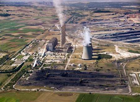 Fossil fuel power plant & coal piles, aerial view photo