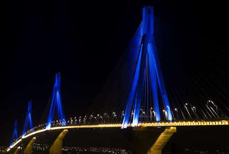 Rio-Antirio bridge over sea, illuminated at night.