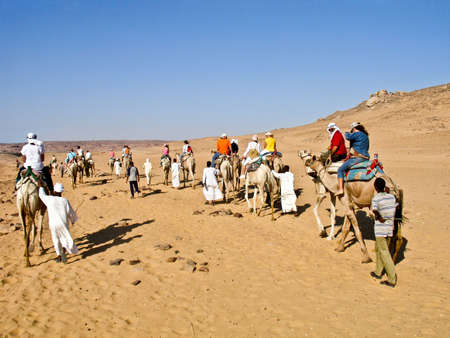 Aswan, Egypt - August 23, 2010: Caravan of tourists in camels crossing the Nubian desert.