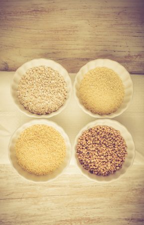 lomography: Types of grain groats on a white wood. Studio shoot with vintage mood.