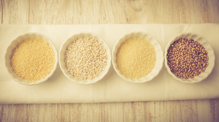 Types of grain groats on a white wood. Studio shoot with vintage mood.