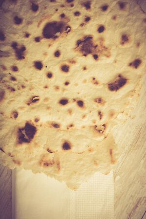 unleavened: Homemade whole wheat flour tortillas on a wooden table. Unleavened bread.