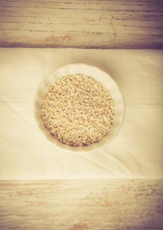 kasha: Barley groats on a white wood. Groats in bowl. Studio shot with vintage mood.