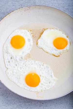 huevos estrellados: Huevos fritos en la sart�n blanco. tiro del estudio Foto de archivo