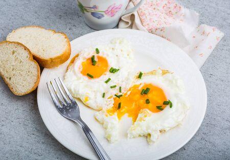 huevos estrellados: Two fried eggs with chives on white plate. studio shot Foto de archivo