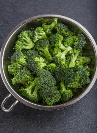 pieces of broccoli in a sieve on a black table. studio shot Reklamní fotografie