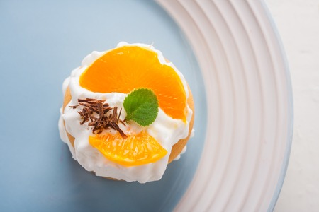 bisquit: small biscuit with orange and whipped cream. studio shot
