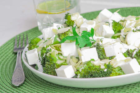 broccoli salad: broccoli salad with feta cheese and almonds on a white plate