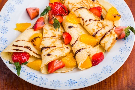 slew: Homemade pancakes with fresh fruit on a white plate. studio shot