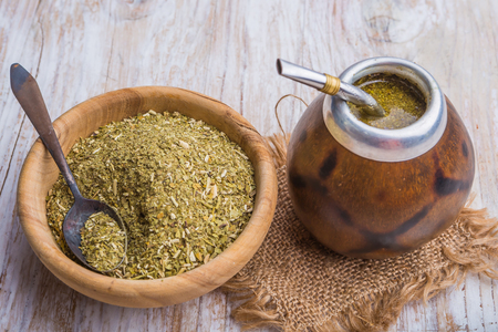 Mate: Yerba mate on a white wooden table. studio shot