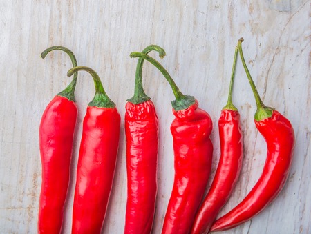 thai chili pepper: Red Hot Chili Peppers on a white wooden table. studio shot Stock Photo