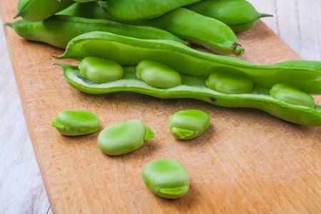 Fresh broad bean on wooden kitchen board. studio shot photo
