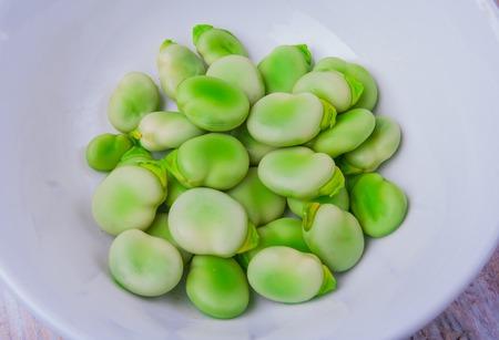 Fresh broad bean in white bowl. studio shot Stock Photo