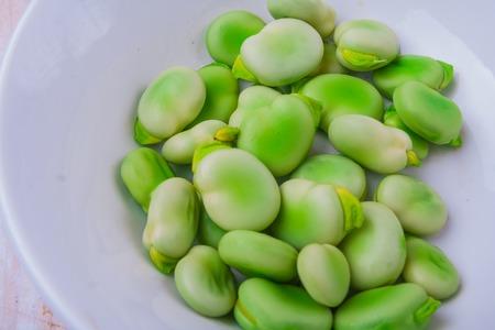 haba: Fresh broad bean in white bowl. studio shot Stock Photo