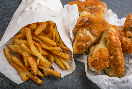 Potatoes fries in a little white paper bag and chicken wings on a black background. studio shot photo