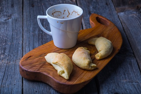 Cup of coffee and homemade yeast croissants on a cutting board photo