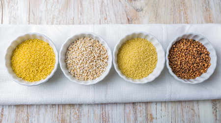 groats: Types of grain groats on a white wood Stock Photo