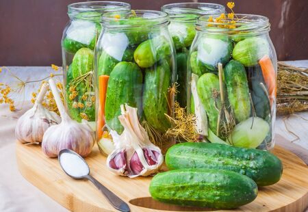 jars of homemade preserves with pickled cucumbers on wooden table photo