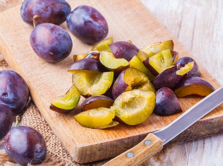 sliced Fresh ripe plums on a wooden cutting board photo