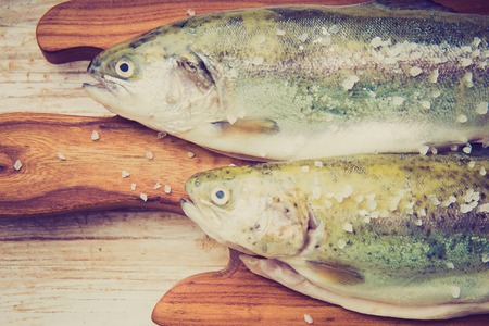 Vintage photo of two rainbow trouts on a cutting board photo