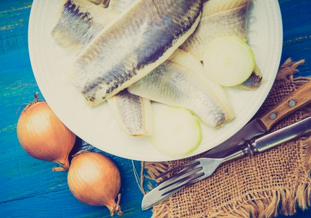 lomography: Vintage photo of herring with onions on a white plate
